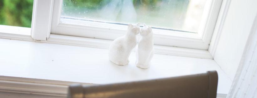 Två porslinskatter i ett fönster